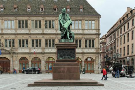 Strasbourg, place Gutenberg. Statue de Gutenberg, bronze, David d'Angers, 1839. Guttenberg, debout près d'une presse d'imprimerie tient un parchemin sur lequel on lit « et la lumière fut » ; le piédestal est agrémenté de quatre reliefs.